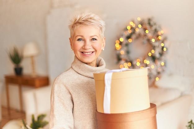 Portret pozytywnej dojrzałej kobiety w swetrze z promiennym szczęśliwym uśmiechem pozuje w przytulnym salonie z świątecznymi dekoracjami, trzymając pudełko z prezentami od syna. wesołych świąt
