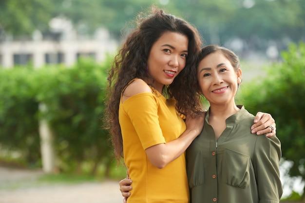 Portret pozytywnej dorosłej wietnamskiej córki obejmującej dojrzałą matkę na ulicy