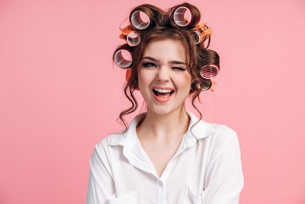 Portret pozytywnej dziewczyny mrugającej na białym tle nad różową ścianą