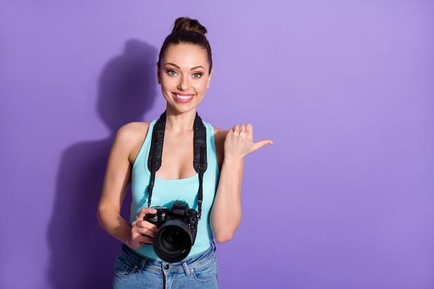 Portret pozytywnej dziewczyny podróżnika trzyma aparat cyfrowy punkt kciuk palec copyspace