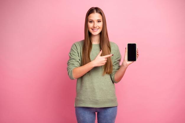 Portret pozytywnej dziewczyny trzymać palec wskazujący smartfona zademonstrować