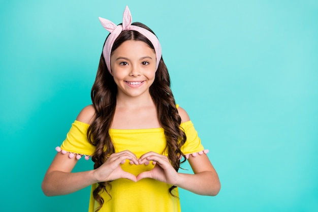 Portret pozytywnej dziewczyny uczynić ręce kształt serca pokaż symbol uczuć miłości