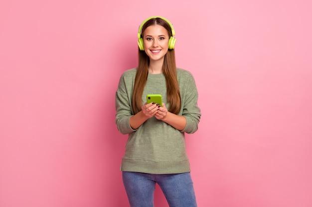 Portret pozytywnej dziewczyny używa zestawu słuchawkowego do słuchania listy odtwarzania telefonu komórkowego