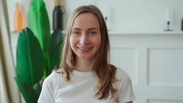 Portret pozytywnej emocjonalnej kobiety, która uśmiecha się, patrząc w kamerę