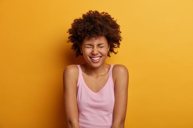 Portret pozytywnej etnicznej kobiety mruży twarz, uśmiecha się radośnie, pokazuje białe zęby, jest w dobrym nastroju, cieszy się wolnym dniem, słucha dobrych dowcipów od przyjaciela, nosi kamizelkę, modelki na żółtej ścianie
