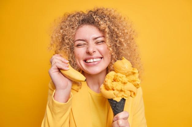 Portret pozytywnej kaukaskiej kobiety uśmiecha się szeroko, pokazuje białe, równe zęby w dobrym nastroju, gdy je ulubiony deser, trzyma banana przy uchu, zamyka oczy z przyjemności odizolowanej nad żółtą ścianą