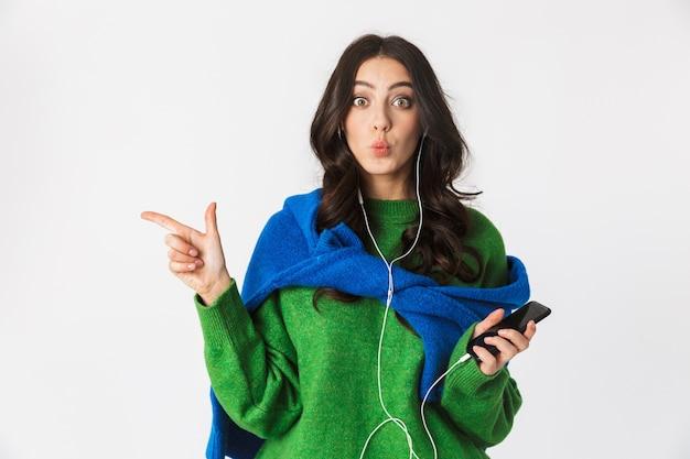 Portret pozytywnej kobiety o ciemnych włosach, noszenie słuchawek i trzymając telefon komórkowy, podczas gdy na białym tle