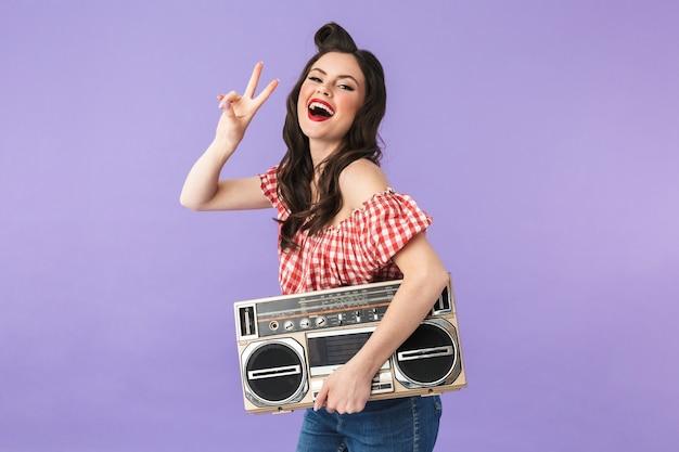 Portret pozytywnej kobiety pin-up w stylu amerykańskim, ciesząc się, trzymając stary vintage boombox na białym tle nad fioletową ścianą