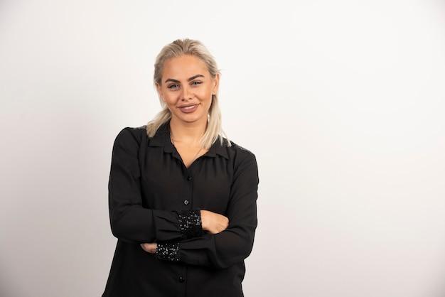 Portret pozytywnej kobiety w czarnej koszuli pozowanie na białym tle. wysokiej jakości zdjęcie