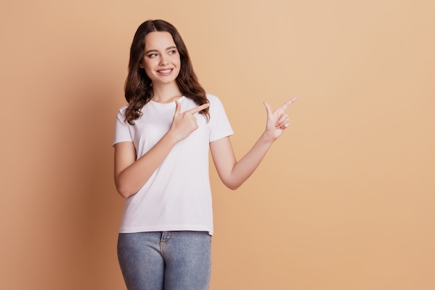 Portret pozytywnej ładnej dziewczyny wskazuje palce puste miejsce na beżowym tle