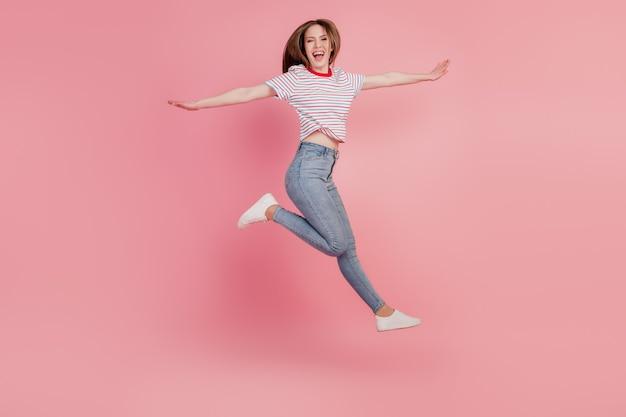 Portret pozytywnej marzycielskiej uroczej damy skaczącej, pozującej ręce, skrzydła na różowym tle