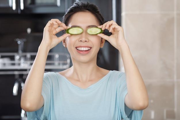 Portret pozytywnej młodej azjatyckiej kobiety zakrywającej oczy plasterkami ogórka w nowoczesnej kuchni