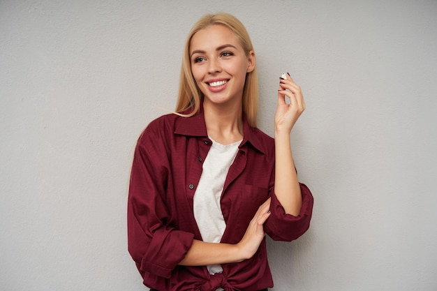 Portret pozytywnej młodej blondynki z przypadkową fryzurą wyjmującą słuchawkę i patrząc na bok z uroczym szerokim uśmiechem, odizolowana na jasnoszarym tle
