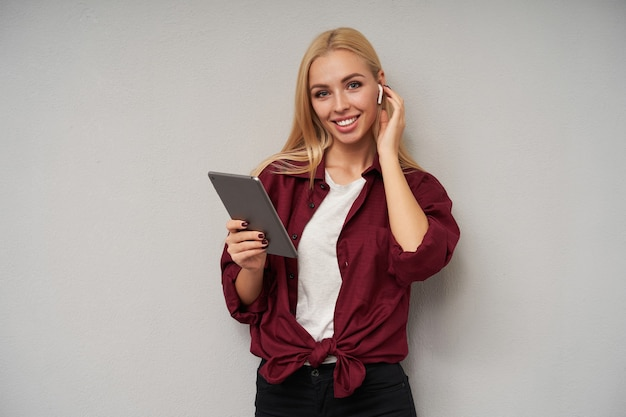 Portret pozytywnej, młodej, długowłosej blondynki pani noszącej słuchawki i trzymającej rękę na uchu, radośnie patrząc na aparat z uroczym uśmiechem, pozująca na jasnoszarym tle