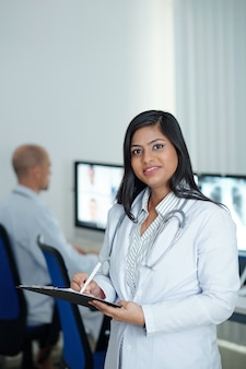 Portret pozytywnej młodej lekarki robiącej notatki w dokumencie po spotkaniu online z kolegami z innych klinik