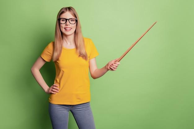 Portret pozytywnej nauczycielki pani ząb rozpromieniony uśmiech przytrzymaj wskaźnik bezpośrednio pusta przestrzeń nosić okulary żółta koszulka