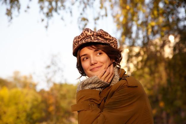 Portret pozytywnej pięknej brązowookiej młodej kobiety z swobodną fryzurą, opierającej brodę na uniesionej dłoni i uśmiechającej się delikatnie, noszącej stylowe ubrania, pozując nad miejskim ogrodem