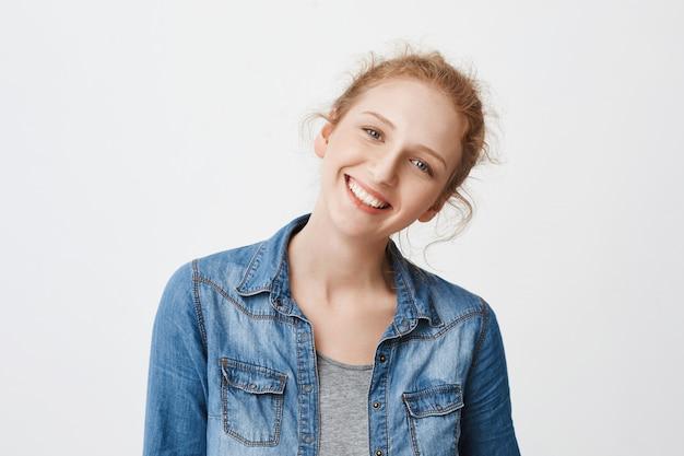 Portret pozytywnej, przyjaznej europejskiej rudowłosej dziewczyny przechylającej głowę w prawo i uśmiechającej się szeroko, patrząc na aparat czystymi niebieskimi oczami