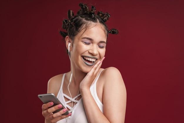 Portret pozytywnej punkowej dziewczyny z dziwaczną fryzurą i ciemną szminką, śmiejąc się podczas korzystania ze smartfona ze słuchawkami izolowanymi na czerwonej ścianie