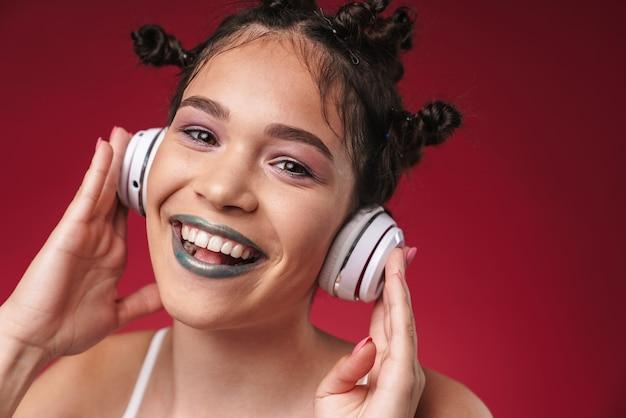 Portret pozytywnej punkowej dziewczyny z dziwaczną fryzurą i ciemną szminką, uśmiechającą się podczas słuchania muzyki przez słuchawki izolowane nad czerwoną ścianą