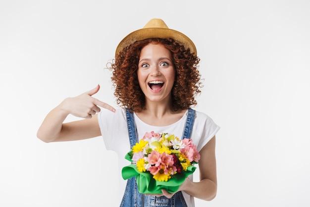 Portret pozytywnej rudowłosej kręconej kobiety 20s w letnim słomkowym kapeluszu uśmiecha się i trzyma pudełko na kwiaty izolowane nad białą ścianą