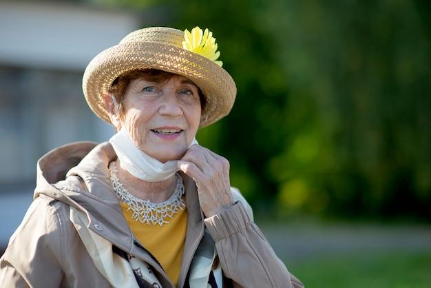 Portret pozytywnej starszej kobiety noszącej maskę na twarz z powodu koronawirusa - styl życia seniorów w okresie wakacyjnym lub jesiennym