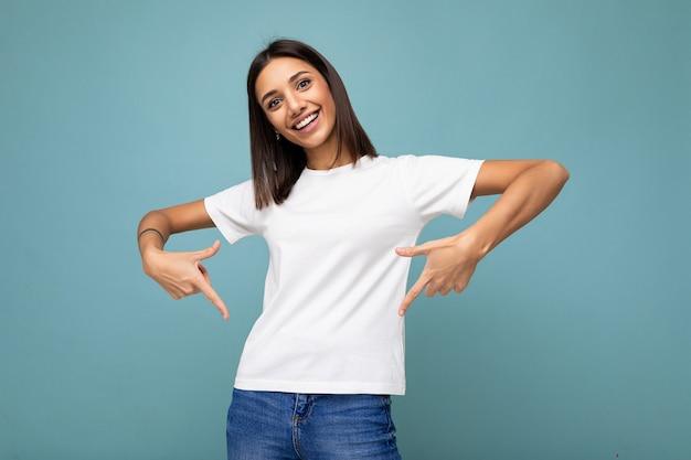 Portret pozytywnej szczęśliwej uśmiechniętej młodej pięknej brunetki z noszeniem szczerych emocji