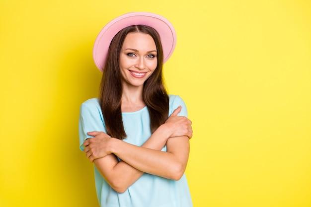 Portret pozytywnej uroczej dziewczyny, która przytula się, cieszy copyspace, nosi dobrze wyglądające ubrania odizolowane na żywym kolorze tła