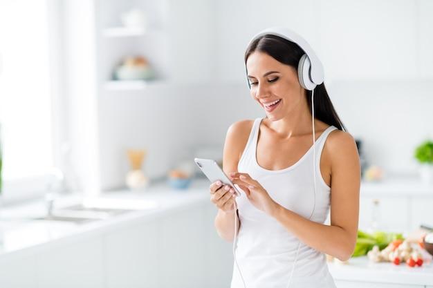 Portret pozytywnej, wesołej dziewczyny, która zostaje w kuchni, słucha muzyki na słuchawkach, używa smartfona, chce znaleźć wybór, co usłyszeć, załóż biały podkoszulek w domu w domu