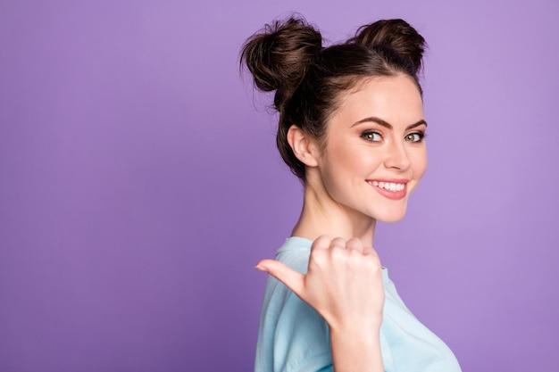Portret pozytywnej wesołej dziewczyny nastoletniej promotora punkt kciuk copyspace obecne wskazówki polecają opinie noszą dobre ubrania wyglądające na białym tle na fioletowym tle