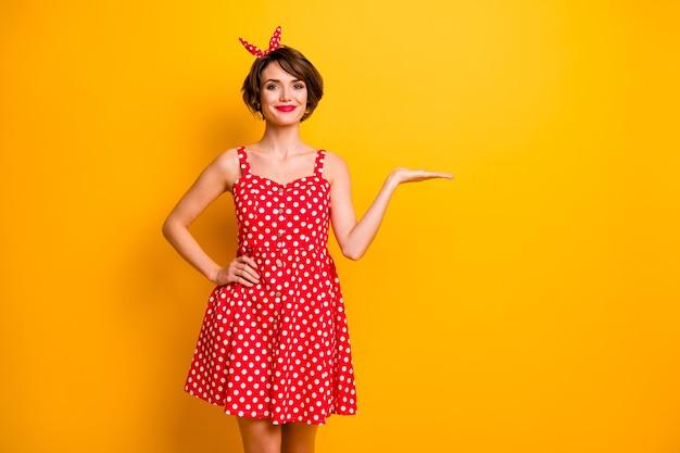 Portret pozytywnej, wesołej dziewczyny promotor trzymać rękę prezentować reklamy promo polecam wybrać sugerować nosić dobry wygląd vintage jasne ubrania odizolowane na żółtej ścianie