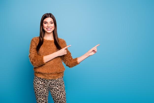 Portret pozytywnej, wesołej dziewczyny promotor wskazujący palec wskazujący miejsce na kopię pokazuj reklamy promocyjne sugerują wybraną jesienną wyprzedaż wiosenną nosić dobrze wyglądające ubrania izolowane na niebieskiej ścianie
