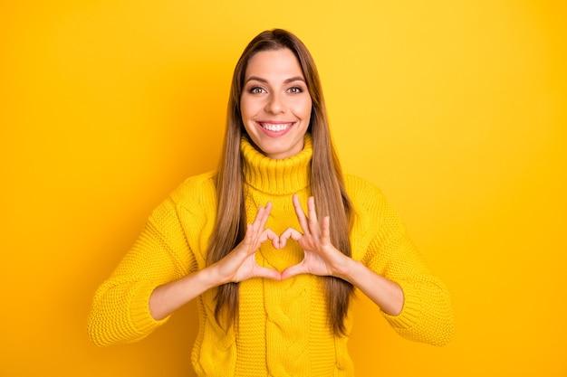 Portret pozytywnej wesołej dziewczyny sprawia, że serce z jej palców jest namiętne na zawsze symbol miłości czuć zadowolenie wyraz twarzy nosić żywy sweter odizolowany na jasnej ścianie