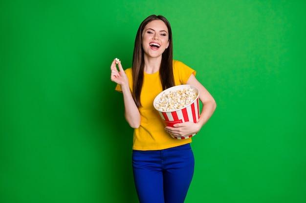 Portret pozytywnej wesołej dziewczyny trzymaj duże pudełko popcornu oglądaj zabawną serię