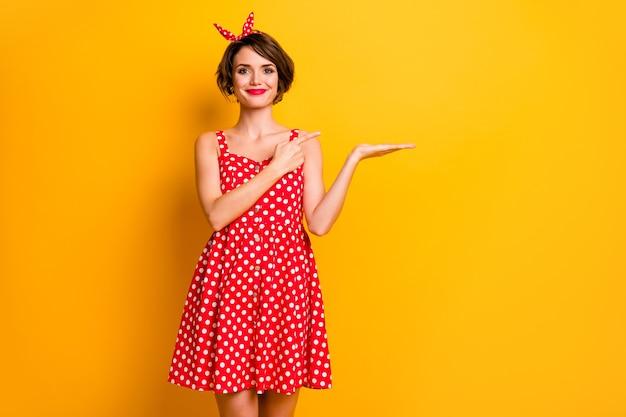 Portret pozytywnej wesołej dziewczyny trzymaj rękę reklamy wyświetlaj promocję palec wskazujący radzę wybrać zdecydować śledzić komentarz odświeżyć nosić czerwoną dobrą wyglądającą spódnicę odizolowaną na żywej kolorowej ścianie