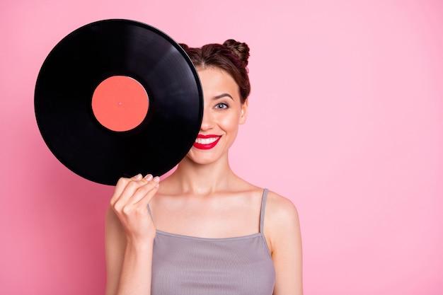 Portret pozytywnej, wesołej dziewczyny ukryj twarz za pomocą okrągłej płyty gramofonowej z płytą winylową, która chce słuchać retro hitów muzycznych, nosić dobrze wyglądające ubrania izolowane na pastelowym kolorze