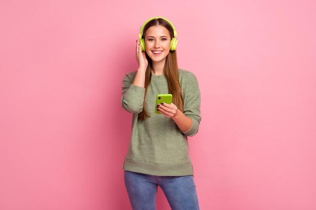 Portret pozytywnej wesołej dziewczyny za pomocą smartfona słuchać muzyki z dźwiękiem stereo