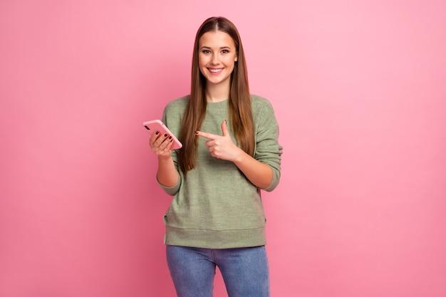 Portret pozytywnej wesołej dziewczyny za pomocą smartfona wskazuje palec wskazujący urządzenia