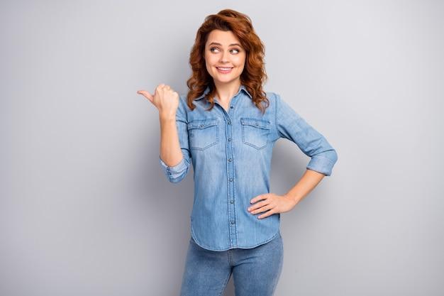 Portret pozytywnej, wesołej kobiety promotor wskazujący palec wskazujący copyspace polecam zasugerować wybrane reklamy promocyjne nosić dobry strój na białym tle na szarej ścianie