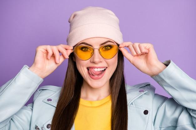 Portret pozytywnej wesołej młodzieży wyobraź sobie pyszne słodkie desery lizać język zęby dotknąć nowoczesne specyfikacje nosić ubrania w stylu casual na białym tle nad fioletowym kolorem tła
