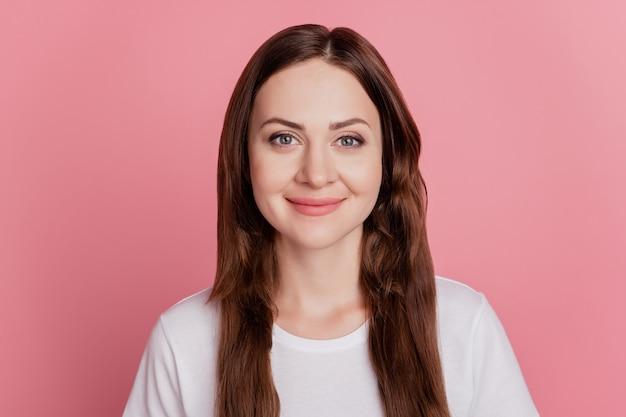 Portret pozytywnej wesołej uroczej uroczej dziewczyny wyglądającej na aparat fotograficzny uśmiech na różowym tle