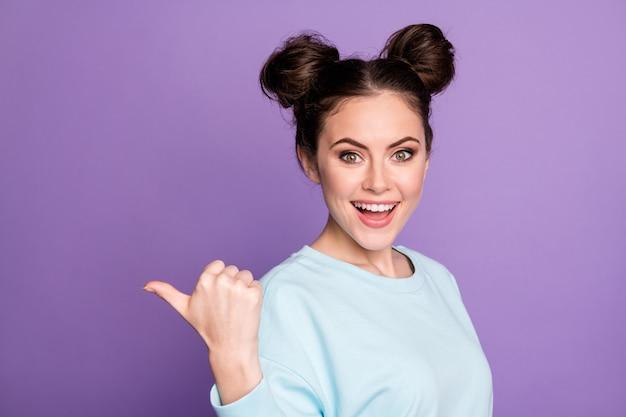 Portret pozytywnej wesołej zszokowanej dziewczyny młodzieżowej promotora point kciuk copyspace wskazuje reklamy promocja obecna sprzedaż wojna dobry wygląd modne ubrania izolowane nad fioletowym kolorem tła