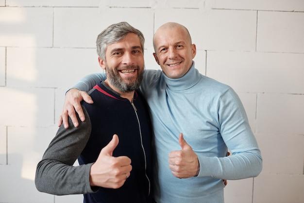 Portret pozytywnie podekscytowany przyjaciół w średnim wieku obejmujący i pokazujący kciuk w górę