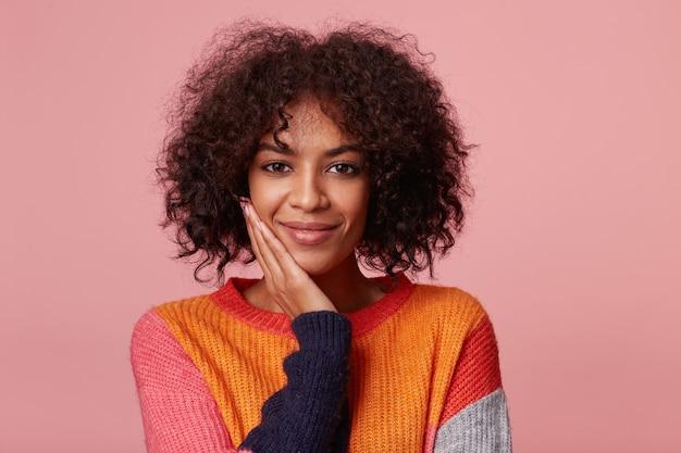 Portret pozytywnie zadowolonej uroczej afroamerykanki z fryzurą afro wygląda z przyjemnością, dotyka jej twarzy dłonią, wygląda na szczęśliwą, ubrana w kolorowy longsleeve, na białym tle