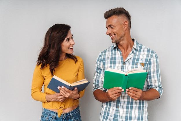 Portret pozytywny optymistyczny szczęśliwy uśmiechający się dorosły kochający para na białym tle nad szarą ścianą czytanie książki.