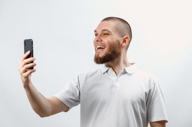 Portret pozytywny przystojny brodaty mężczyzna w białej koszulce rozmawia przez telefon za pomocą smartfona