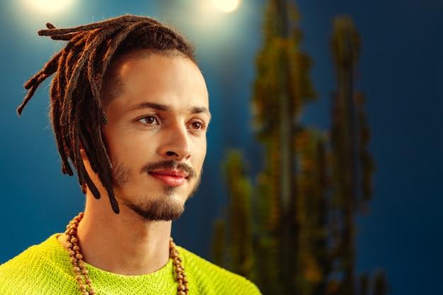 Portret pozytywny przystojny caucasian facet z dreadlocks przeciw błękitowi
