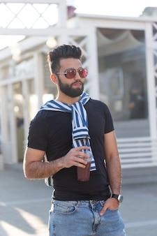Portret pozytywny wesoły młody arab ze szklanką soku ze słomką podczas spaceru w parku w ciepły słoneczny letni dzień. koncepcja odpoczynku po nauce i pracy w weekendy.