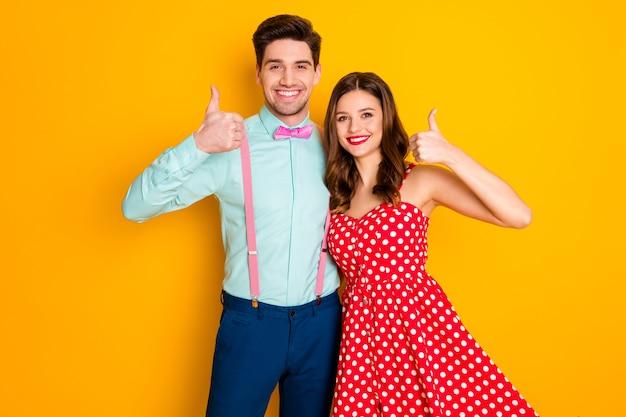Portret pozytywnych wesołych małżonków obejmuje kciukiem w górę znak up