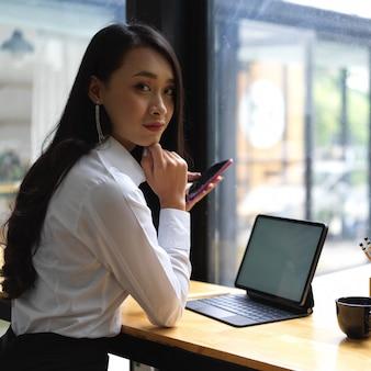 Portret pracownica patrząc na kamery podczas pracy ze smartfonem i tabletem w kawiarni